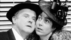 Black and White image of man and woman cheek to cheek in vintage clothes
