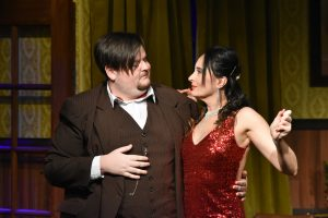 Man in brown suit embraces woman in sparkly red dress
